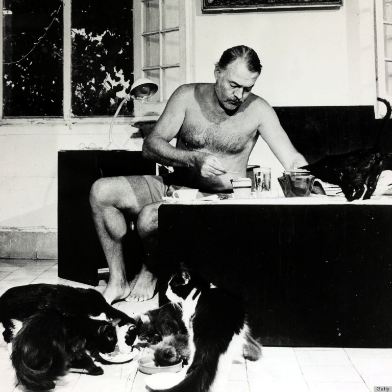 Literature Personalities. pic: circa 1940's. Author Ernest Hemingway pictured at breakfast with a group of cats feeding at his feet. Ernest Hemingway, (1899-1961) US writer of novels and short stories and Nobel Prize winner, was also a keen sportsman. He